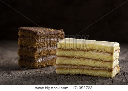 Two slice of cake one with cocoa cream and the other with vanilla and cheese cream on wooden background