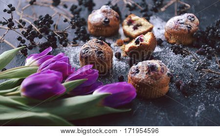 Muffin With Currants On A Dark Background Next To The Berries On The Branches. And A Bouquet Of Flow