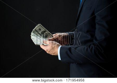 people, business, finances and money concept - close up of businessman hands holding dollar cash over black background