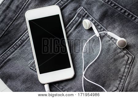 technology, clothes and music concept - smartphone and earphones on pocket of denim pants or jeans