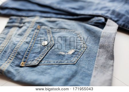 clothes, wear and fashion concept - close up of denim pants or jeans with pocket on white background