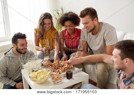 friendship, holidays, fast food and celebration concept - happy friends with drinks and snacks eating pizza at home