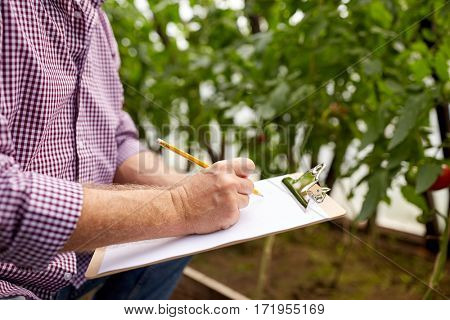 farming, gardening, agriculture and people concept - senior man writing to clipboard at farm greenhouse