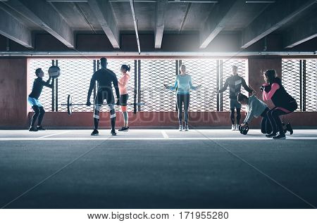 Group Of Sporty People Training Indoors.