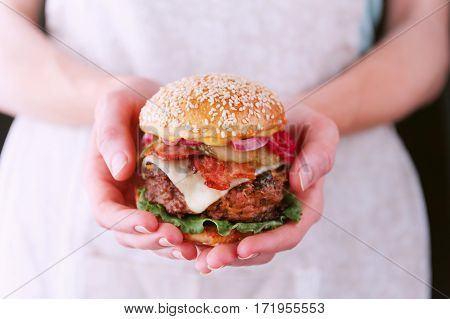 Woman Chef Holding A Cooked Her Delicious And Juicy Homemade Burger In A Rustic Style With A Big Cho