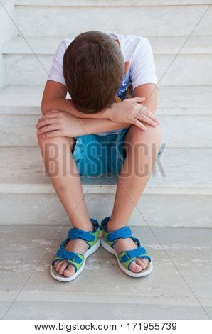 Sad child sitting on stairs with his head down