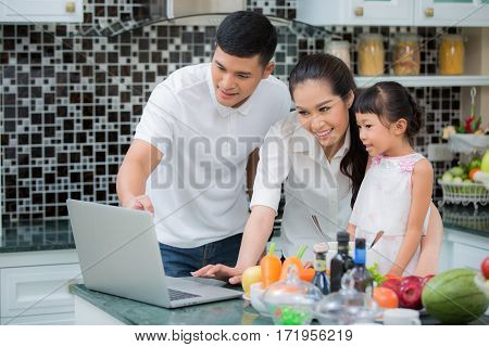 Asian Family Kitchen Lifestyle father mother and Daughter cooking food my use manu in internet