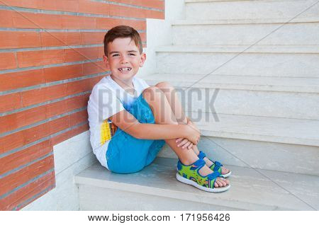 7 year old boy sitting on staairs
