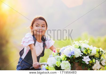 Portrait of a beautiful Asian girl holding bouquet of flowers in the park while riding a vintage bycicle Thai asia children concept.