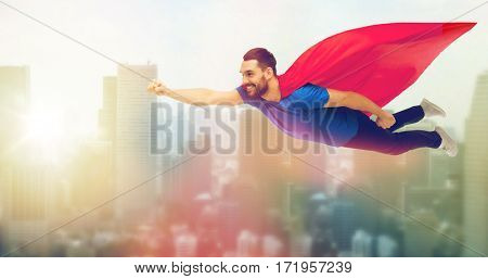 freedom, power, motion and people concept - happy man in red superhero cape flying in air over singapore city skyscrapers background
