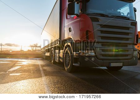 transportation, freight transport and vehicle concept - close up of truck on parking