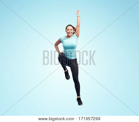 sport, fitness, motion and people concept - happy smiling young woman jumping in superhero pose over blue background