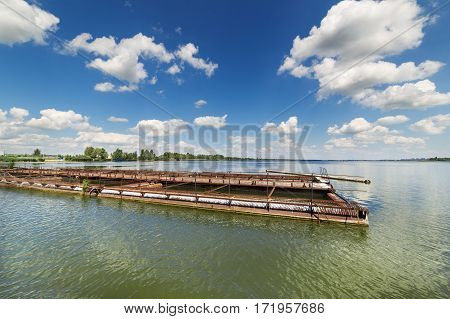 The cages for breeding fish. Fish farm on a big lake.