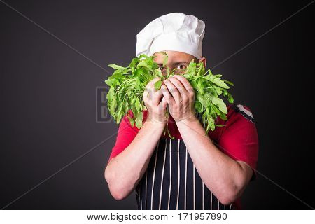 Closeup of happy chef holding arugula beam on black background