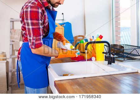 Man Makes Cleaning The Kitchen. Young Man Washes The Dishes. Cleaning Concept.