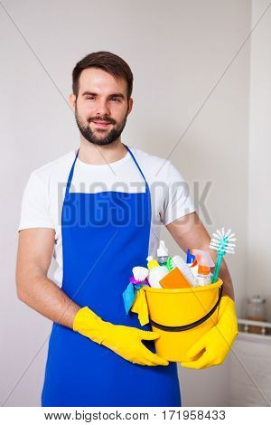 Man Holding Plastic Bucket With Bottles And Brushes, Gloves And Detergents In The Kitchen