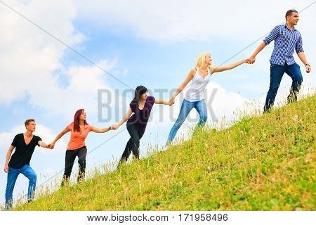young people helping each other climb a hill
