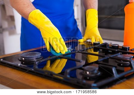 Young Men In Rubber Protective Cleaning And Polish Cooker. Black Shiny Surface Of Kitchen Top, Hands