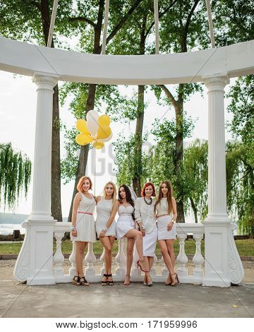 Five Girls With Balloons At Hand Weared On White Dresses On Hen Party Against White Columns Of Arch.