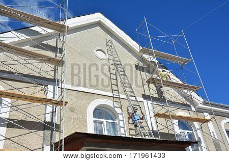 Painting and Plastering Exterior House Scaffolding Wall. Facade Thermal Insulation and Painting Works During Exterior Renovations. Builder Worker Plastering House Facade.