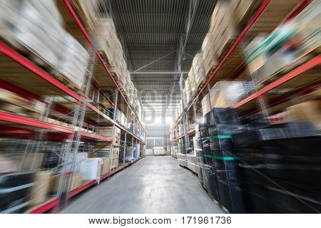 Large industrial warehouse. Long shelves with a variety of boxes and containers. The effect of motion blur.
