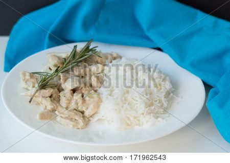 Homemade chicken cooked with white sauce and rosemary and white rice served on a classic plate with blue kitchen towel
