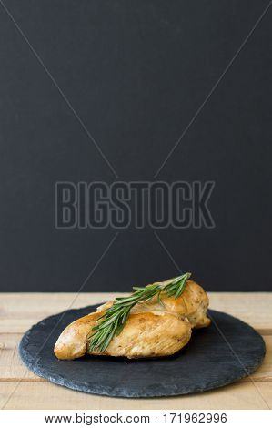 Vertical background with roasted chicken breast decorated with fresh rosemary leaves and served on black slate plate