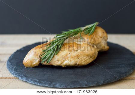 Fried chicken breast with fresh rosemary on small slate board on wooden table black background