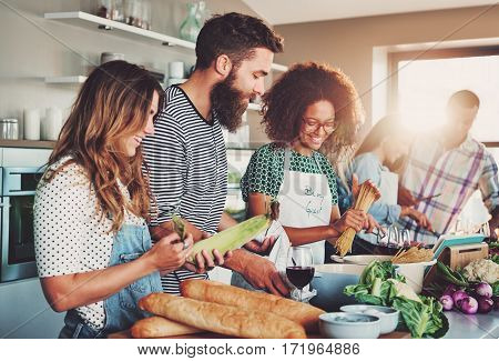 Friends Preparing Food At Table In Kitchen