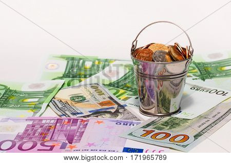 Bucket with Russian small coins stands on theeuro and dollar. Concept of exchange rates
