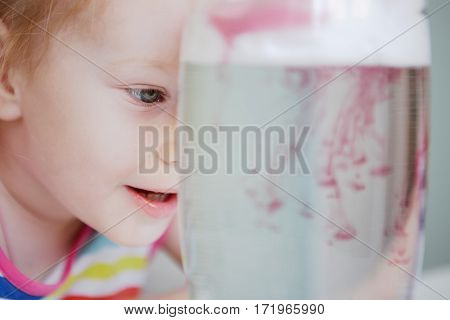 little girl watches through a layer of foam shaving paint seeps