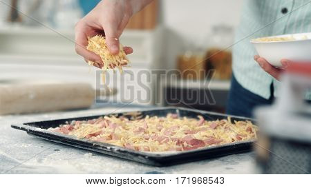 Chef hand sprinkle pizza with cheese, cooking food