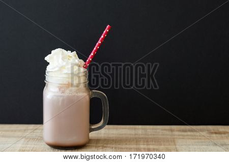 Jar with hot chocolate drink with whipped cream and red paper straw with polka dot pattern