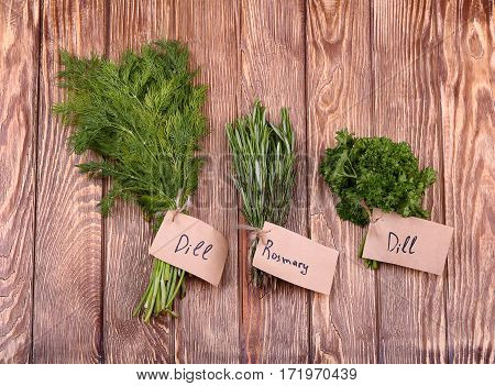 Different fresh herbs on light wooden background