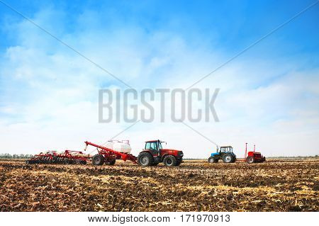 Tractors with tanks working in the field. Agricultural machinery and farming.