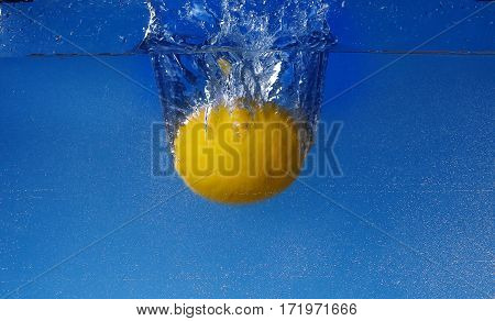 Whole Lemon Dropped In Water Against Gradient Blue Background