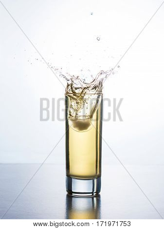 Yellow apple juice in glass with ice cube splashing into liquid against white background. Juice with splash on white background
