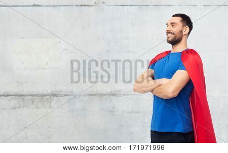 power and people concept - happy man in red superhero cape over gray concrete wall background