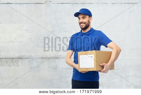 delivery service, mail, people, logistics and shipping concept - happy man with parcel box over gray concrete wall background