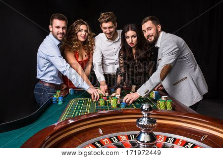 Group of young people behind roulette table on black background. Young people are betting in the game. Young people looking at the camera