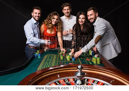 Group of young people behind roulette table on black background. Young people are betting in the game. Players looking to the camera poster