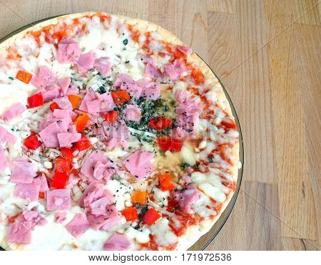Part of prepared appetizing pizza with bacon and cheese and vegetables on round plate on sandy brown wooden kitchen table top view close-up