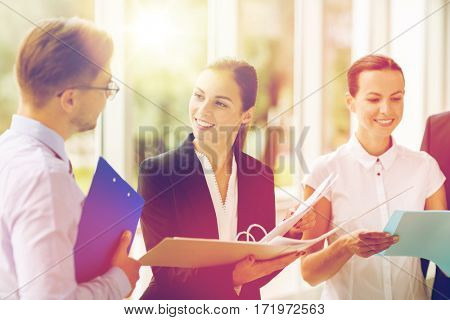 people, work and corporate concept - business team with folders meeting at office