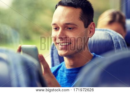 transport, tourism, road trip and people concept - happy young man sitting in travel bus or train with smartphone