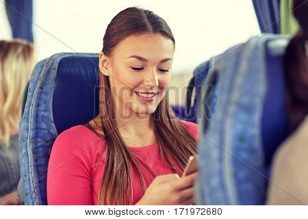 transport, tourism, road trip and people concept - happy young woman sitting in travel bus with smartphone