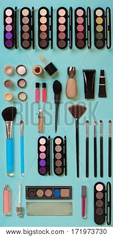 cosmetics for facial makeup: brushes, powder, lipstick, eye shadow, trimmer and other accessories on blue background top view. Beauty flat lay concept