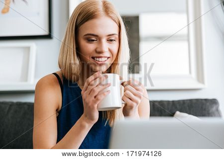 Portrait of happy beautiful young woman drinking coffee at home
