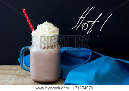Glass with hot chocolate with whipped cream topping and red party straw on wooden table with blue kitchen towel with hand-drawn lettering black background