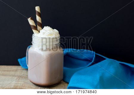 Background with big jar of hot chocolate with whipped cream and two wafer sticks on wooden kitchen table with blue napkin. Homemade hot drinks. Winter breakfast