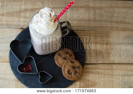 Portion of hot chocolate with whipped cream topping and red straw served on black slate board with chocolate cookies and hearts. Love and romantic concept. St. Valentine Day